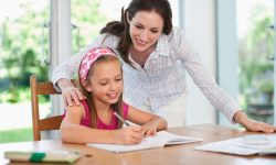 Mother assisting girl (8-9) with school homework